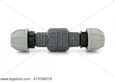 Plastic non return value compression fitting used in plumbing to facilitate the flow of liquid in one direction only on white background.