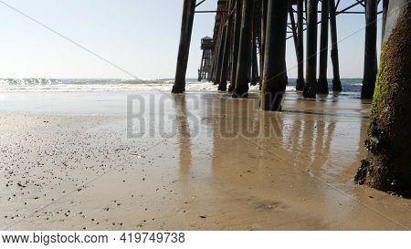 Wooden Piles Under Boardwalk, Old Pier In Oceanside, California Coast Usa. Pilings, Pylons Or Pillar