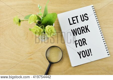 Top View Of Flower, Magnifying Glass And Notebook Written With Let Us Work For You