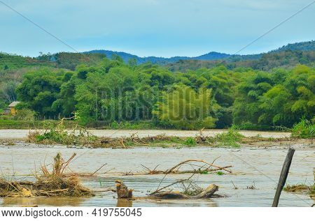 View Of Water Overflowing Banks Of Flooded Pegalan River Benches In Water Landscape Of Malaysia Rain