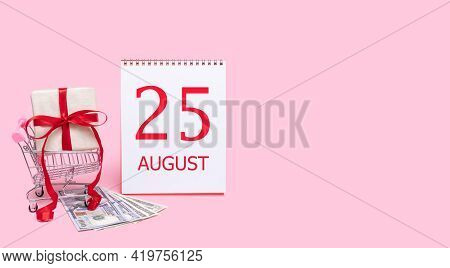 25th Day Of August. A Gift Box In A Shopping Trolley, Dollars And A Calendar With The Date Of 25 Aug