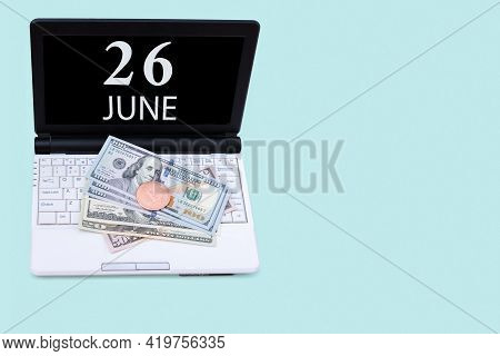26th Day Of June. Laptop With The Date Of 26 June And Cryptocurrency Bitcoin, Dollars On A Blue Back