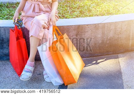 Cropped Shot View Of Young Woman Holding Shopping Bags And Credit Card In Her Hands After Shopping I