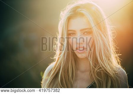 Portrait Sensual Woman In The Nature Background. Sunny Day. Portrait Of Serious Desire Woman. Young