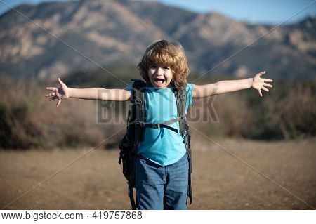 Child Boy With Backpack Hiking In Scenic Mountains. Kid Local Tourist Goes On A Local Hike.