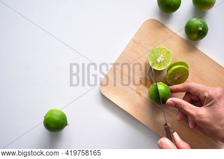 Sliced Lime. Cook Hand Holding Knives Slicing Green Lemon On Wooden Cutting Board With White Backgro