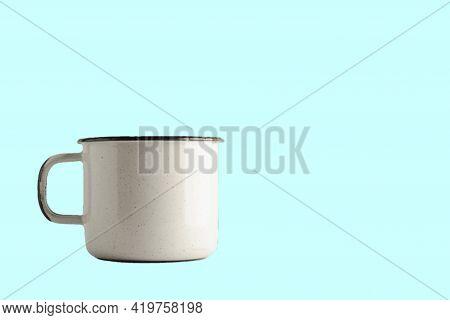 Isolated Vintage White Enamel Mug On Light Blue Background. Suitable For Your Drinks Design Element.