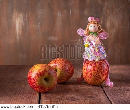Fabulous Postcard. Scatter Red Apples And An Apple Fairy In A Pink Dress Sitting On An Apple