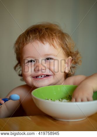 Launching Child Eat. Happy Baby Eating Himself With A Spoon. Smiling Baby Eating Food. Healthy Nutri