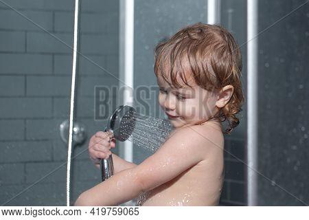 Kid Having Fun To Bath. Cute Baby Boy Enjoying Bath And Bathed In The Bathroom.