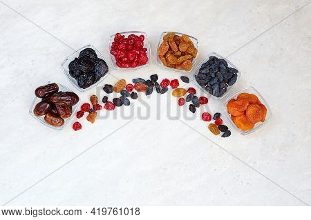 Different Dried Fruits: Prunes, Raisins, Dates, Dried Apricots And Cherries In A Bowls On A Light Ba