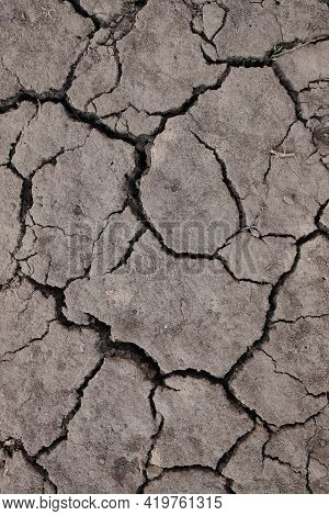 Dry Ground Texture. Close-up Land, Sand, Clay, Black Earth. The Land Is Cracked From Drought. Close-