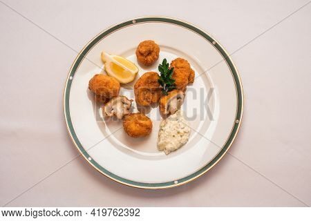 Breaded Fried Button Mushrooms With Tartar Sauce And A Lemon Wedge, Viennese Style Baked Champignons