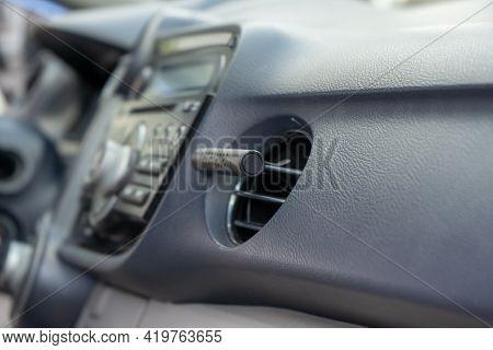 Air Freshener In Car Vent,black Interior, Close Up. Car Air Freshener Mounted To Ventilation Panel,