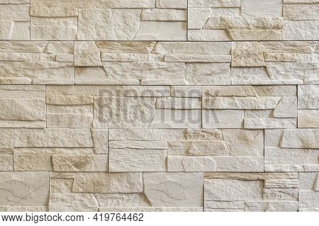 Decorative Stone Wall. Interior Stone Tiles Backdrop. Wall From Light Beige Decorative Stones
