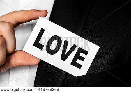 Inscription Love On A White Business Card. A Man In A Black Business Suit Lowers Or Removes From His