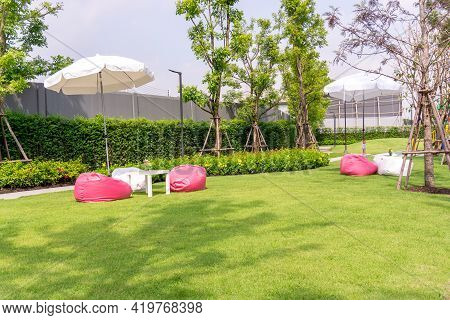 Garden Of Smooth Green Grass Lawn With White And Pink Beanbag Under White Umbrella, Trees, Shrub, In