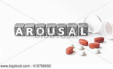 Word Arousal Is Made Of Stone Cubes On A White Background With Pills. Medical Concept Of Treatment,