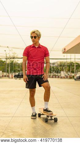 Asian Handsome Man Surf Skate Or Skateboard In Summer Holiday. Young Man Stand On Skateboard At Skat