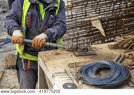Worker With Hand Tool For Bending Rebar