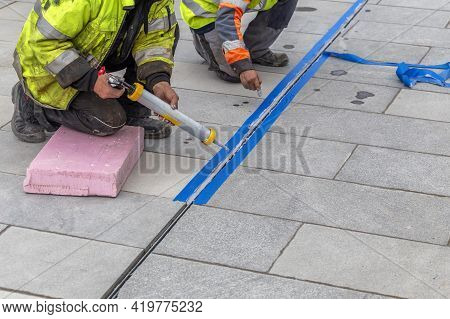 Workers Applying Silicone Sealant With Silicone Gun