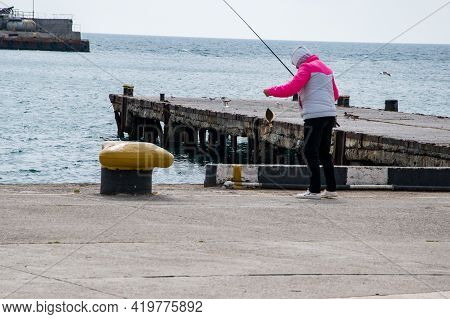 On The Seashore, On The Pier, A Woman Caught A Flounder With A Rod. The Fisherman Caught Fish With A