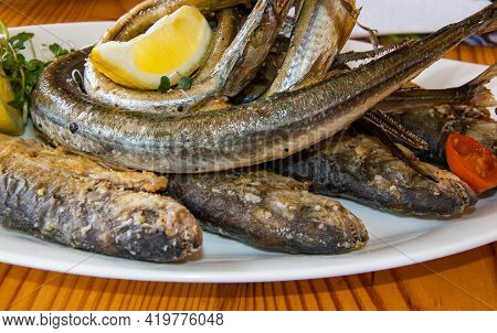 Fried Garfish And Bluefish On A White Plate With Lemon And Microgreens. Fried Predatory Fish. Sargan
