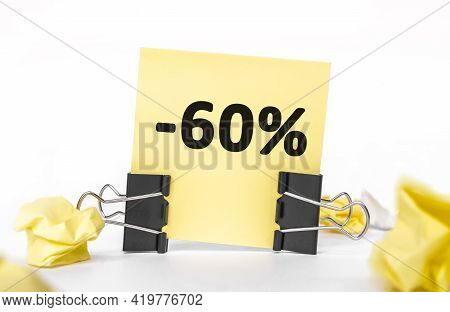 Minus 60 Percent Inscription On A Yellow Piece Of Paper For Notes. Stationery Paper Clips, Crumpled