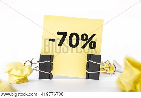 Minus 70 Percent Inscription On A Yellow Piece Of Paper For Notes. Stationery Paper Clips, Crumpled