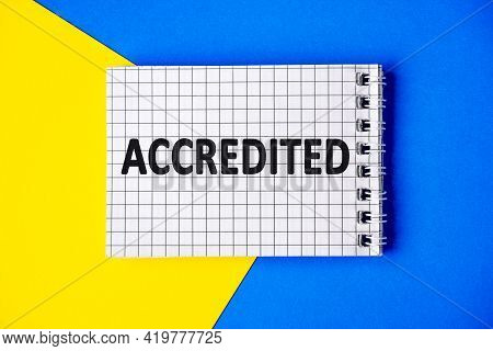 Text Accredited On Page Notebook With Cage Lies On A Blue And Yellow Background, Top View. Of Person