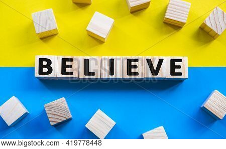Word Believe On Wooden Cubes With Word On Beautiful Yellow And Blue Background. Business, Media Mark