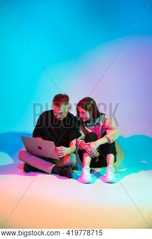 Modern Young Couple With Laptop Sitting On Floor In Colorful Neon Studio Light Working, Playing Or S