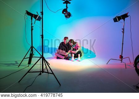 Creative Team Young Girl And Boy With Laptop Working In Photostudio With Photography Equipment. Colo