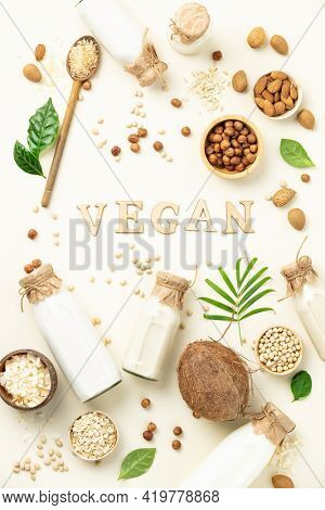 Vegan non dairy plant based milk in bottles and ingredients on light background almond, hazelnut, rice, oat, soy with vegan lettering. Alternative lactose free milk substitute. Top view