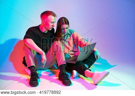 Cool Team Young Girl And Guy Working On Laptop Creating Design Project. Colored Neon Studio Light