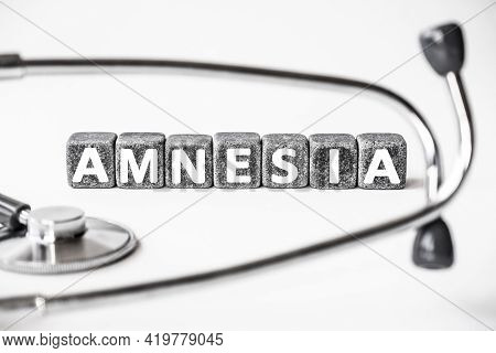 Stone Block Form Word Amnesia With Stethoscope. White Background. Medical Concept. Unusual Memory Lo