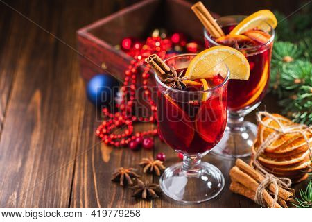 Hot Christmas drink of wine, fragrant spices and fruits in a glass on a wooden rustic background with Christmas decorations, copy space. Holiday hot mulled wine or punch.