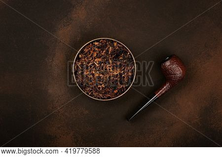 Close Up Round Tin Full Of Ready Rubbed Long Coarse Cut Tobacco Blend And Handmade Briar Smoking Pip