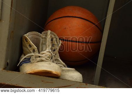 Close Up Pair Of Old Worn Sport Sneakers Shoes And One Basketball Ball In Locker, Low Angle View