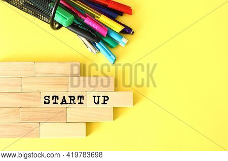 Wooden Blocks Stacked Next To Pens And Pencils On A Yellow Background. Startup Text On A Wooden Bloc