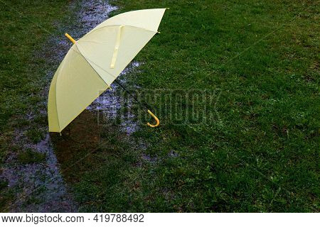 A Yellow Umbrella Lies In A Stream From The Rain On The Wet Grass-the Concept Of Rainy Spring Days