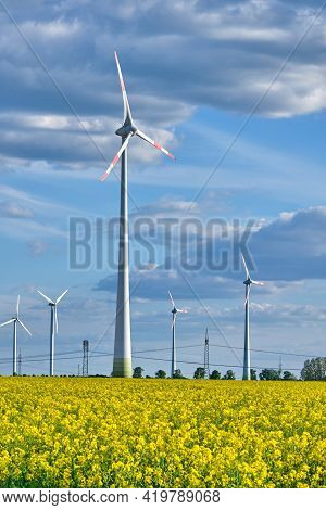 Wind Turbines In A Flowering Canola Field Seen In Germany