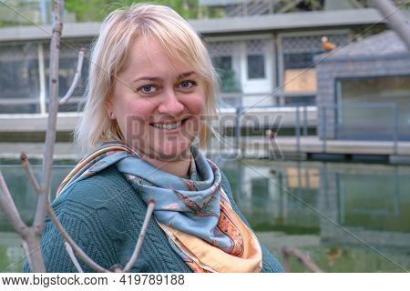 Portrait Of A Middle-aged Woman With Blond Hair Against The Backdrop Of A Pond And A Country House.