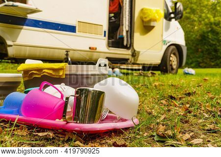Many Clean Dishes Drying Outdoor Against Camper Vehicle. Washing Up On Fresh Air. Camping On Nature,