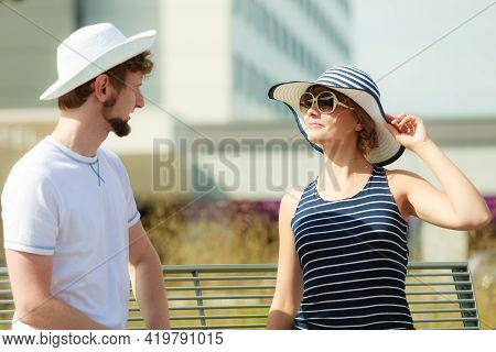 Tourists Couple Sitting On City Bench Resting. Happy Woman And Man Enjoying Life Summer Vacation Out