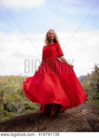 Bali Trend Photo. Caucasian Woman In Long Red Dress Standing On Big Stone In Tropical Rainforest. Va