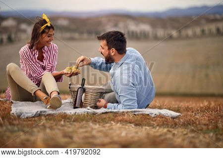 A young couple is enjoying grapes and wine on the picnic on a large meadow on a beautiful day. Relationship, together, love, picnic