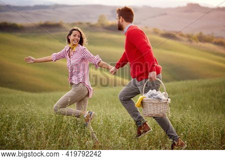 A young excited couple running on a meadow holding by hands while going to picnic on a beautiful sunny day. Relationship, love, together, picnic, nature