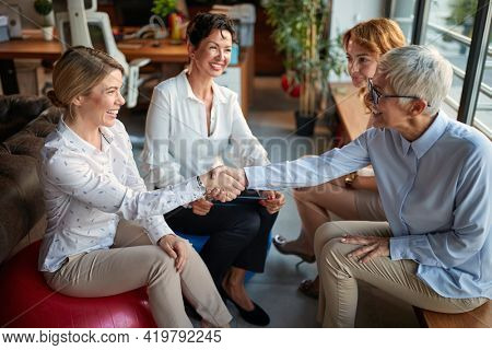 A young female office worker at her new job is getting know with group of female colleagues while taking a break in a friendly atmosphere at workplace. Business, office, job