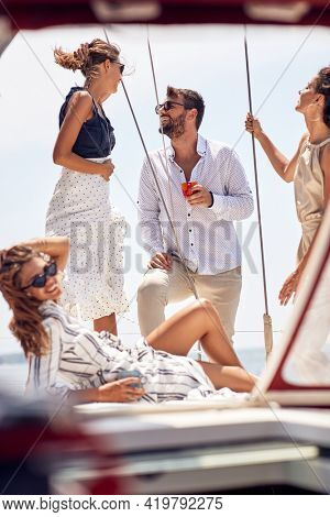 A group of young thoughtful handsome models is having a wonderful time on the sun while is posing for a photo on the deck of the yacht on a beautiful day on the seaside. Summer, sea, vacation,